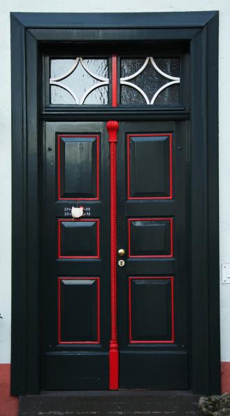 Dunkle Haustüre mit rot eingefassten Einlagen